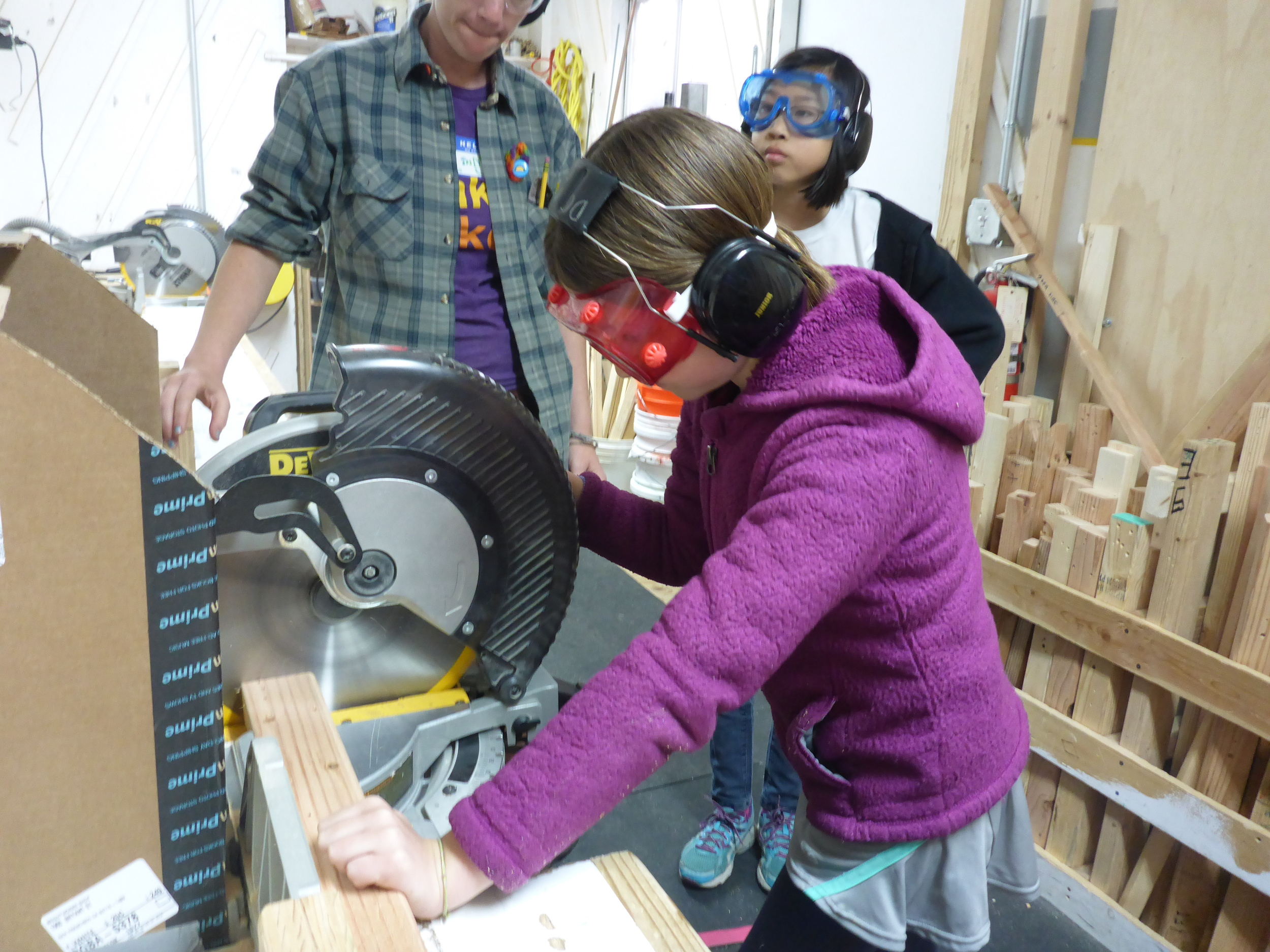 Lily mindfully practices using the chopsaw.