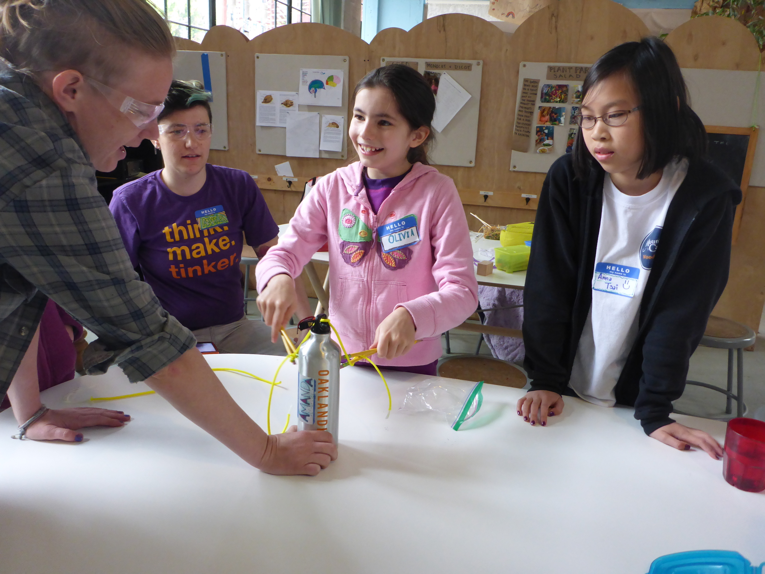 Lindsay, Amanda, Olivia and Anna try to tie a length of paracord around a water bottle just using pencils as chopsticks.
