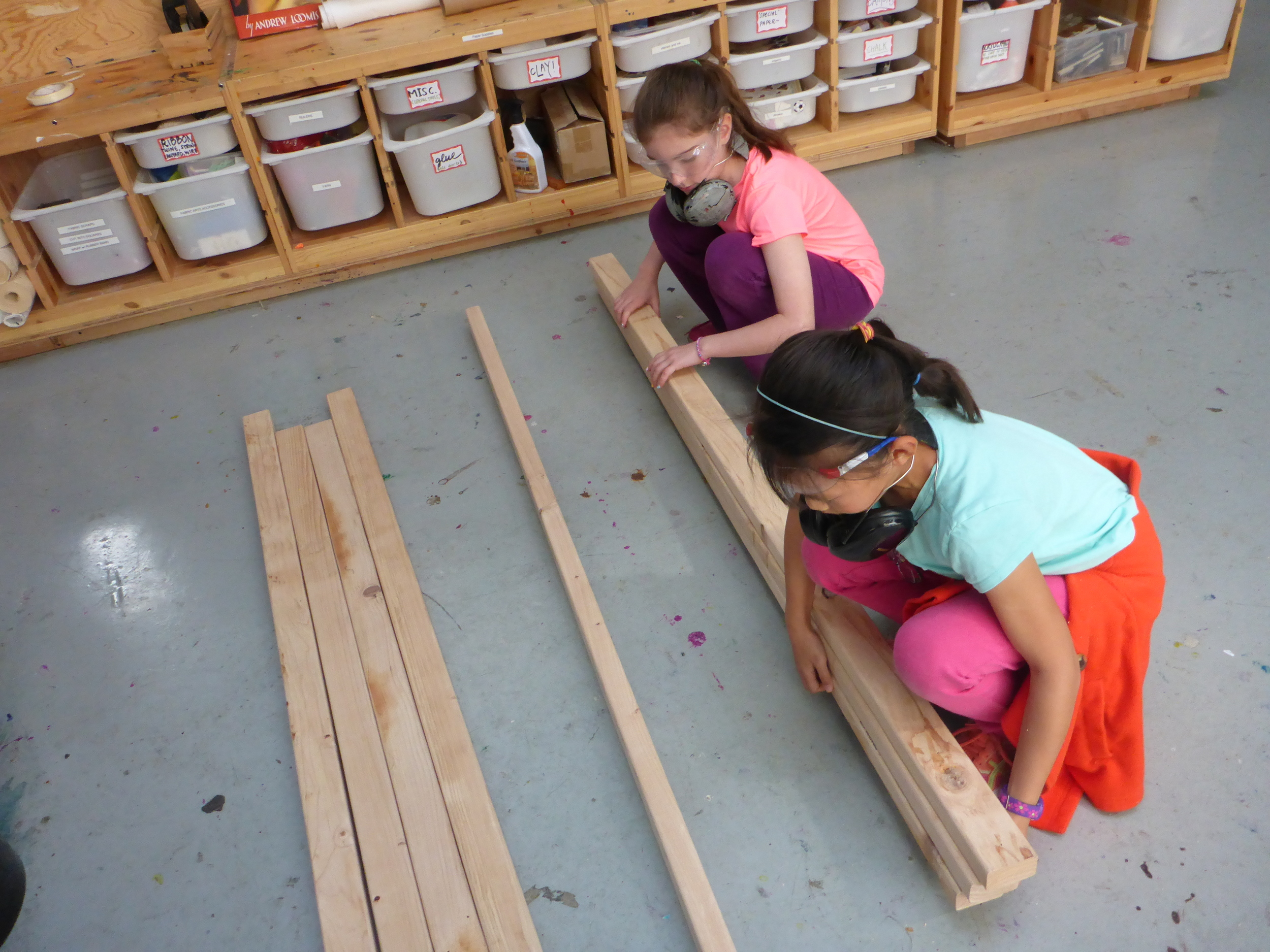 Rin and Belle work together to collect wood that is the size we need and is already cut from previous projects!