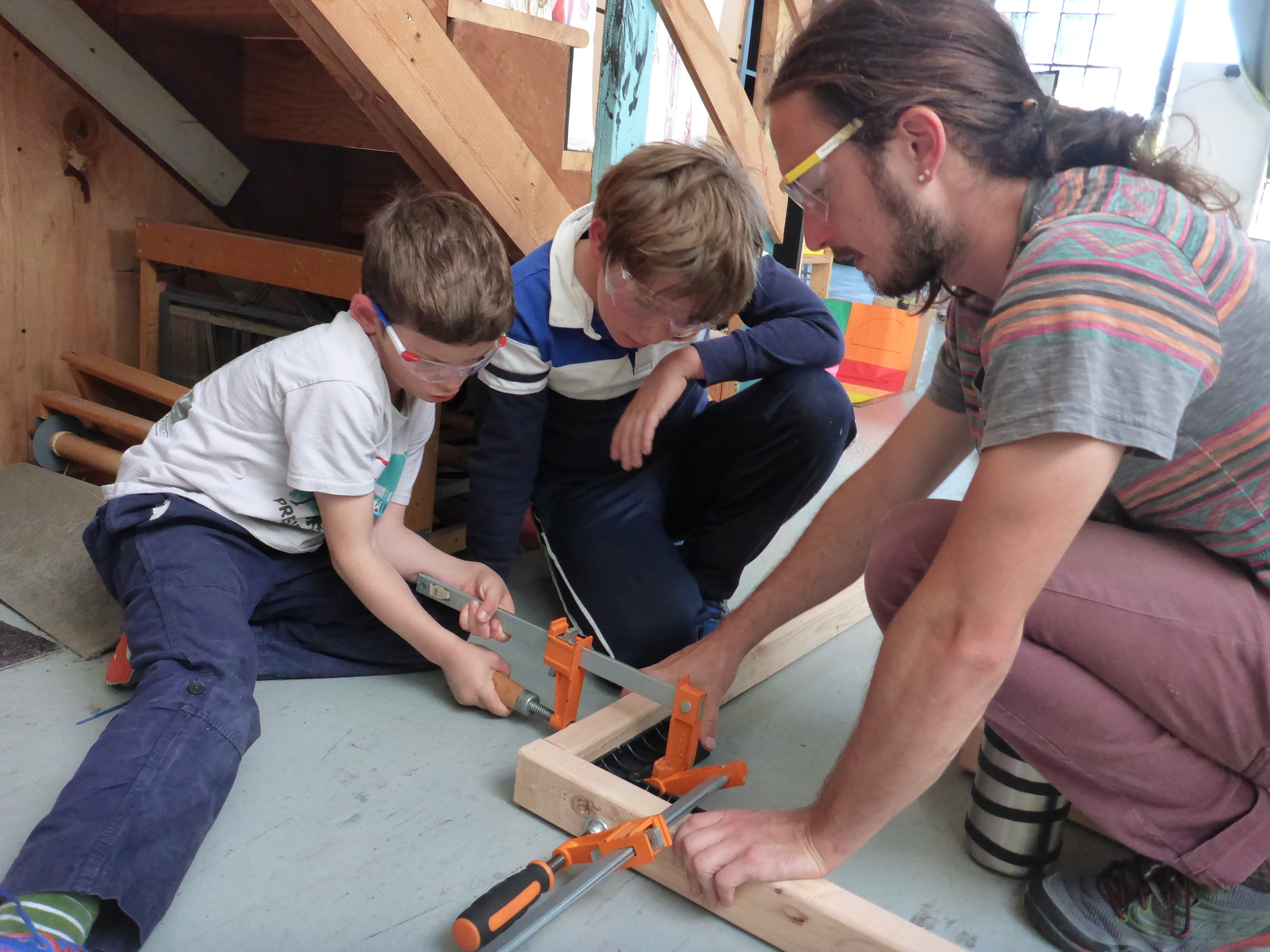 Casper, Alex and Evan figure out how to use the clamps and a square to make a nice square corner.