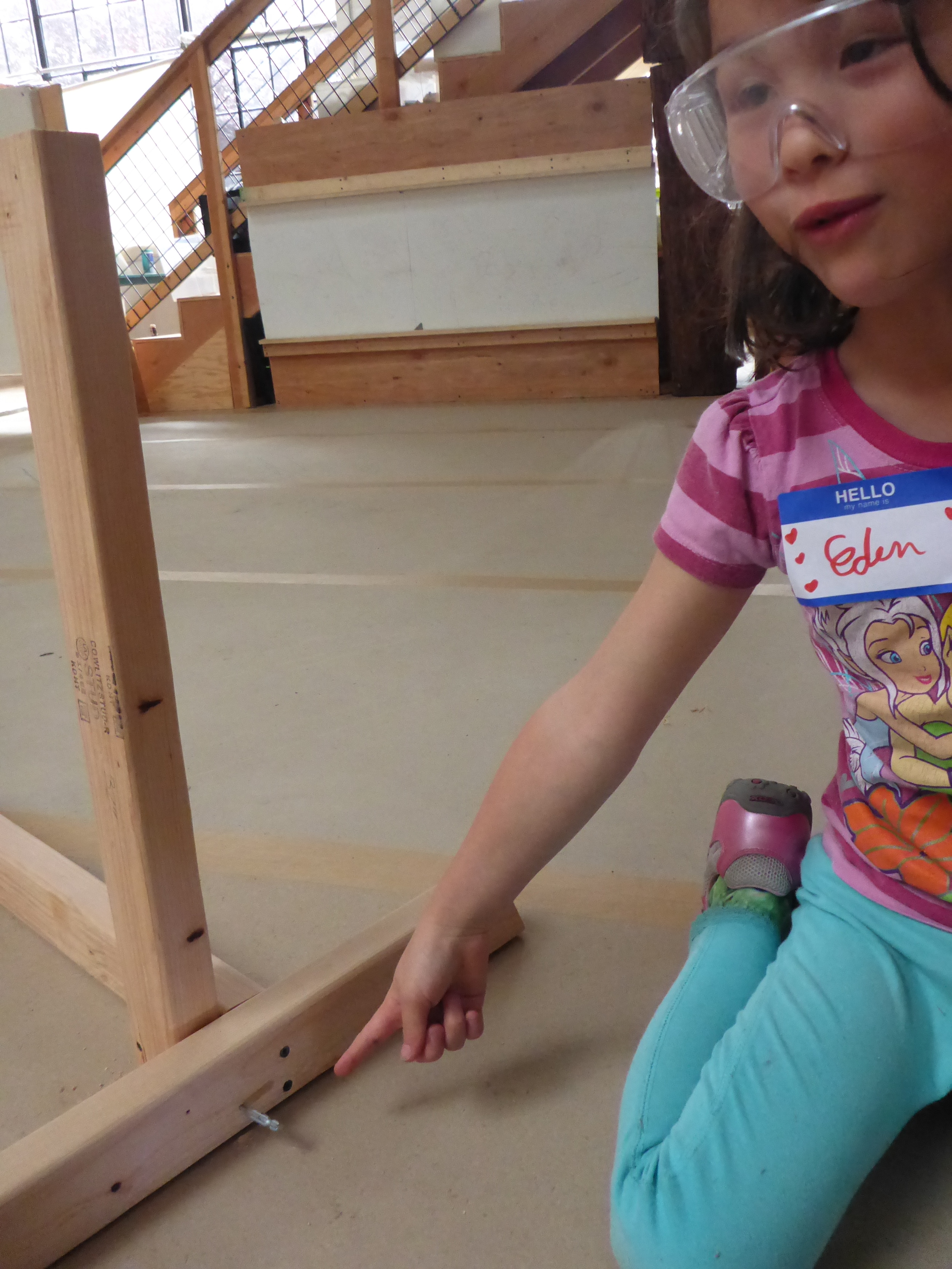Eden shows her teamates how the drill bit wasn't locked into her drill before she started drilling.