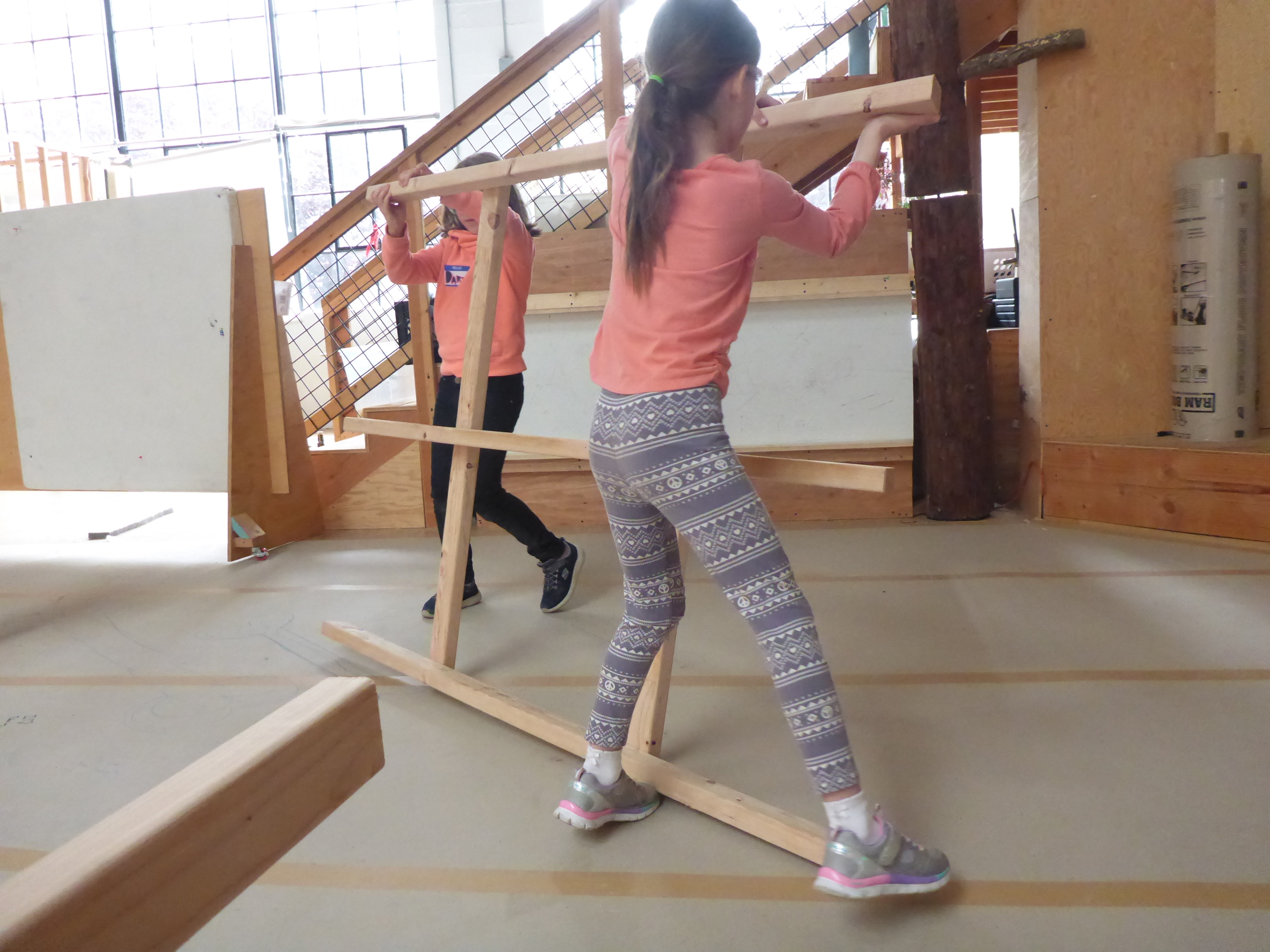 Daria and Lily helping the frame they made perform cartwheels, so it will match up with the other frame!