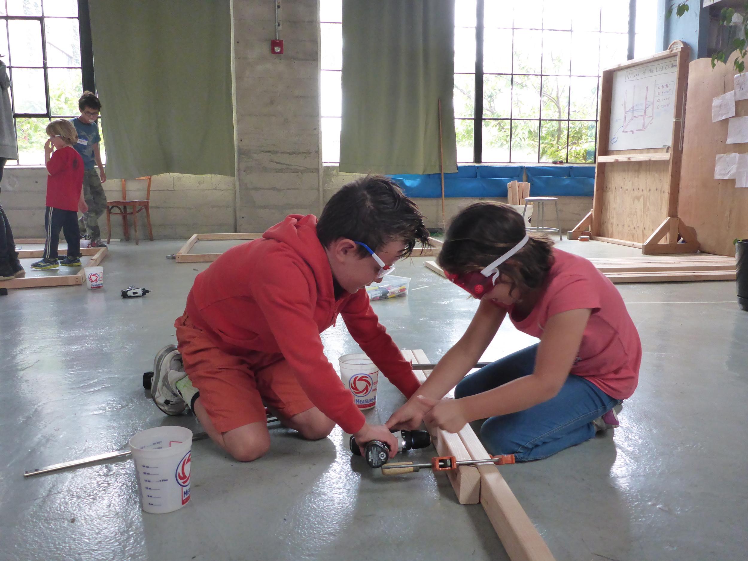 Maya and Mathew work on the Treehouse frame.