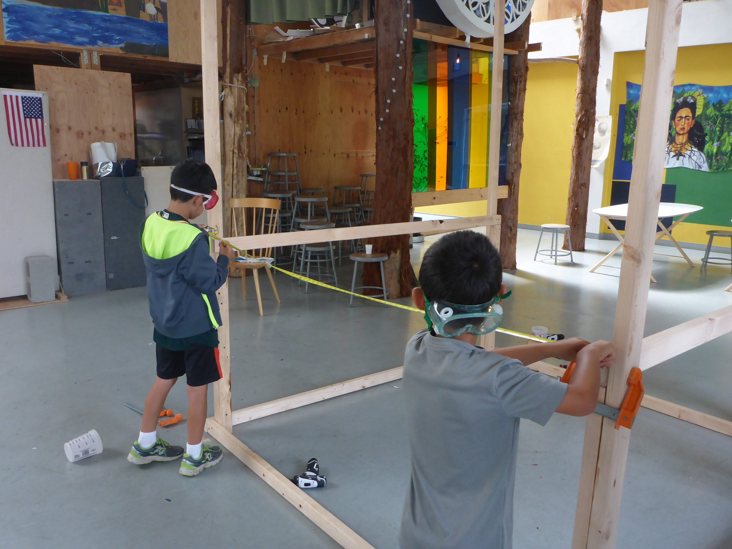 Connor and Haruki measure the distance the floor supports need to cover.