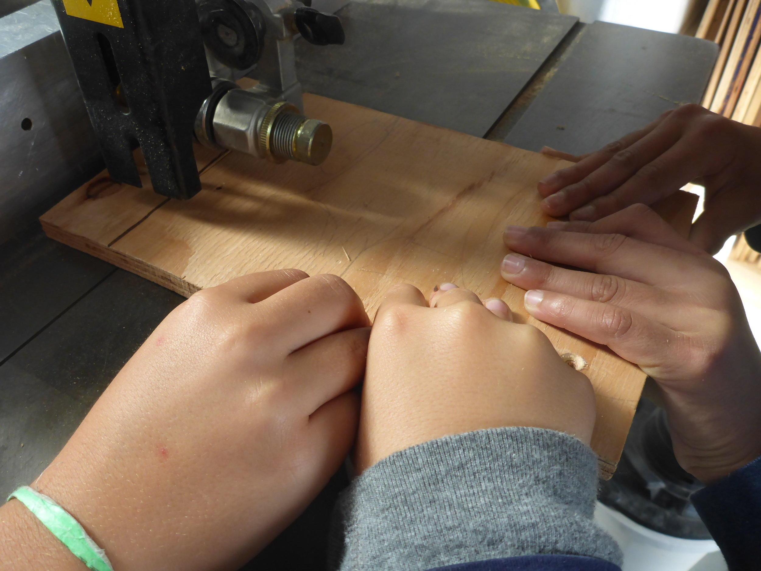 Nolan, Raj and Jaro learn how to use the bandsaw and work together to cut out the pieces for their sleeve.