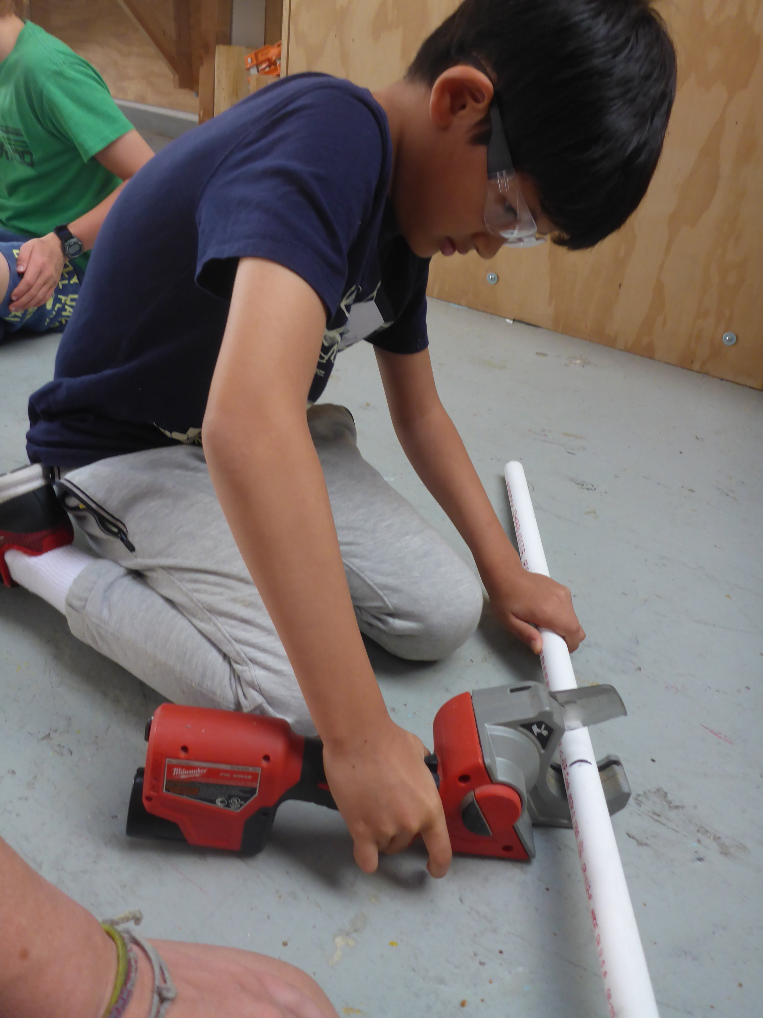 Munir learns how to use a PVC cutter and uses it to cut down the long pieces into more manageable lengths.