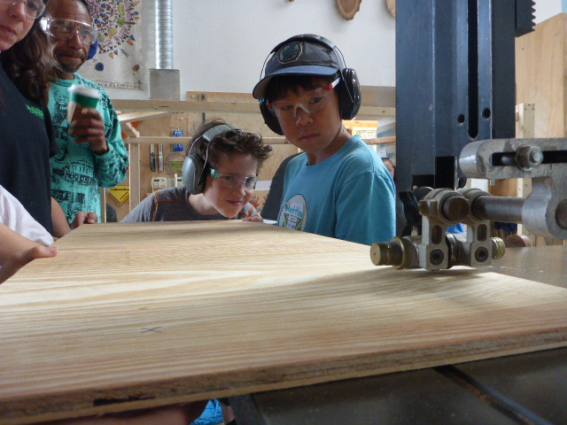 Lyosha concentrates super hard at lining up a cut on the bandsaw with the help of Matthew and Lena.