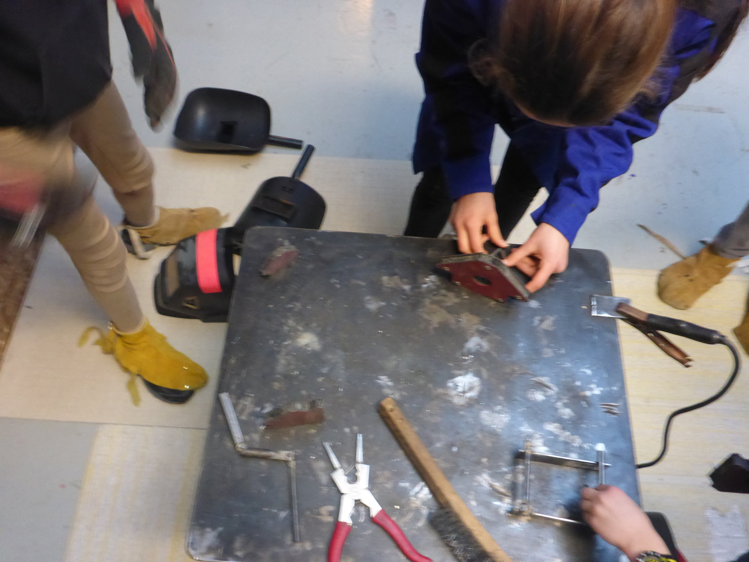 Many busy hands setup their welds on the table, so that the welding gun can move quickly from one person to the next.