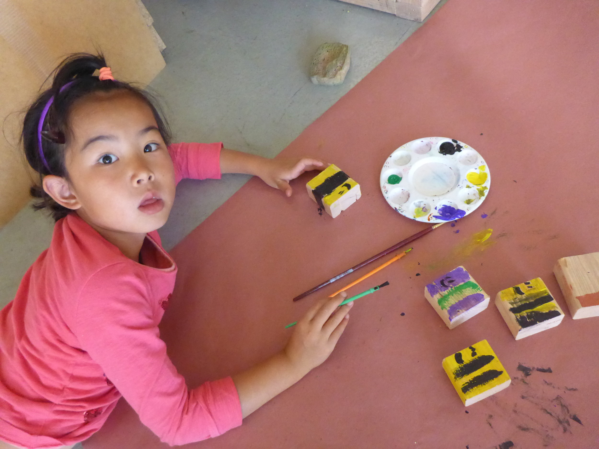 Lilly paints some tiny bees.