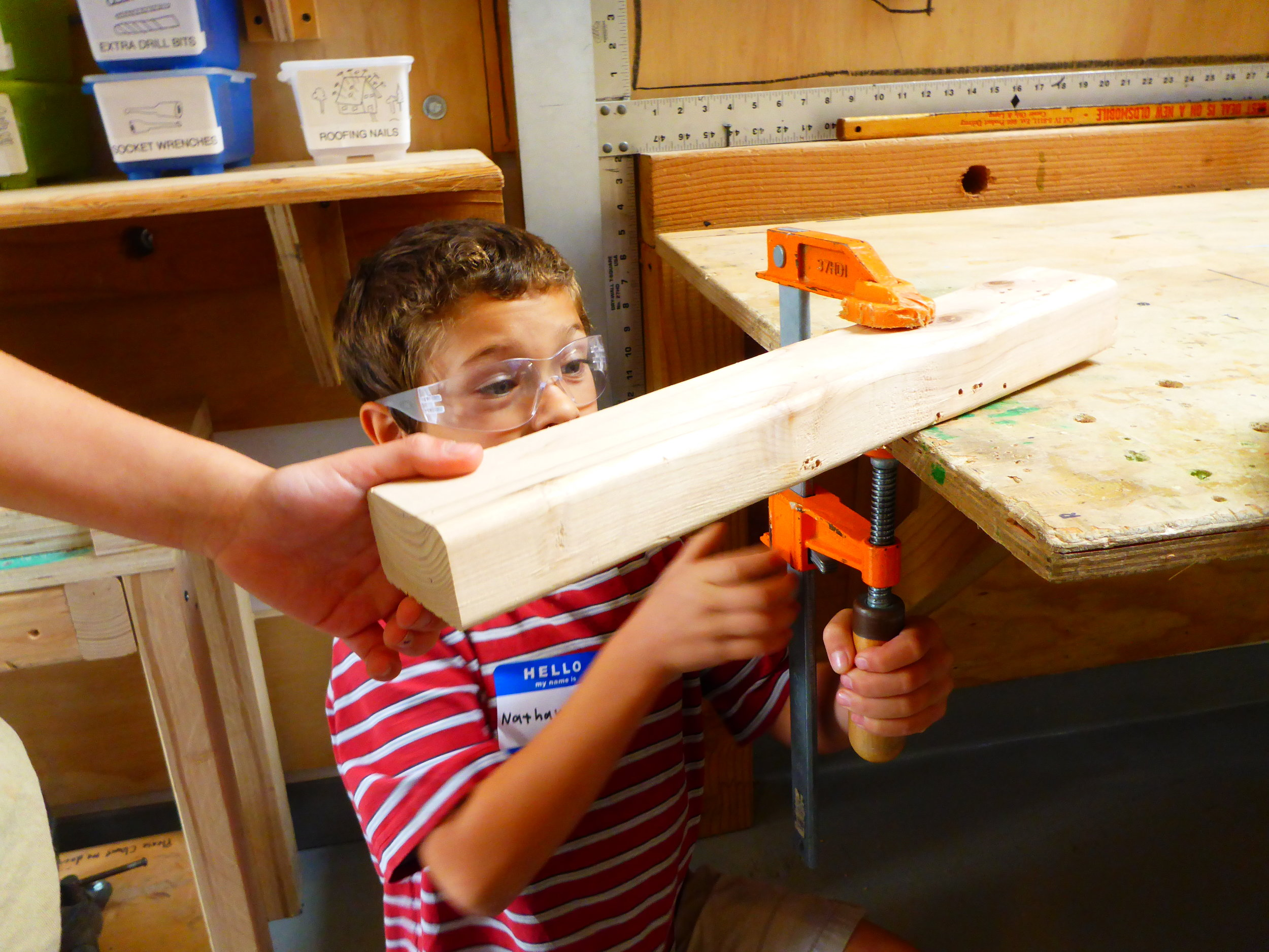 Clamp practice begins with teamwork and clamping wood to the table. Nathanael receives some help from a team mate as he lines up and tightens his clamp.