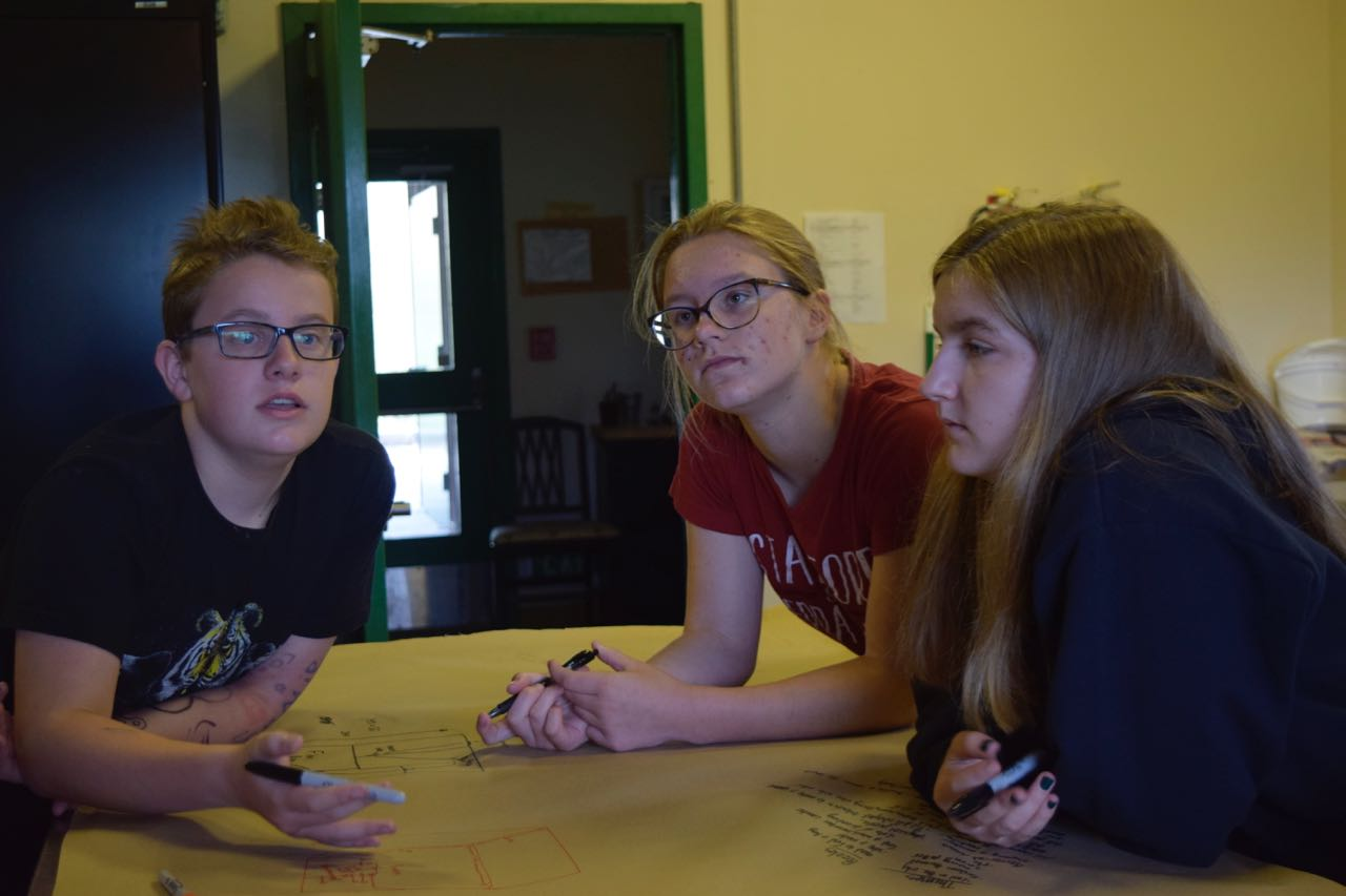Nooi takes their design meeting to the kitchen for extra protection against accidental eavesdroppers. Ft. Reilly, Merritt, and Sarah P.