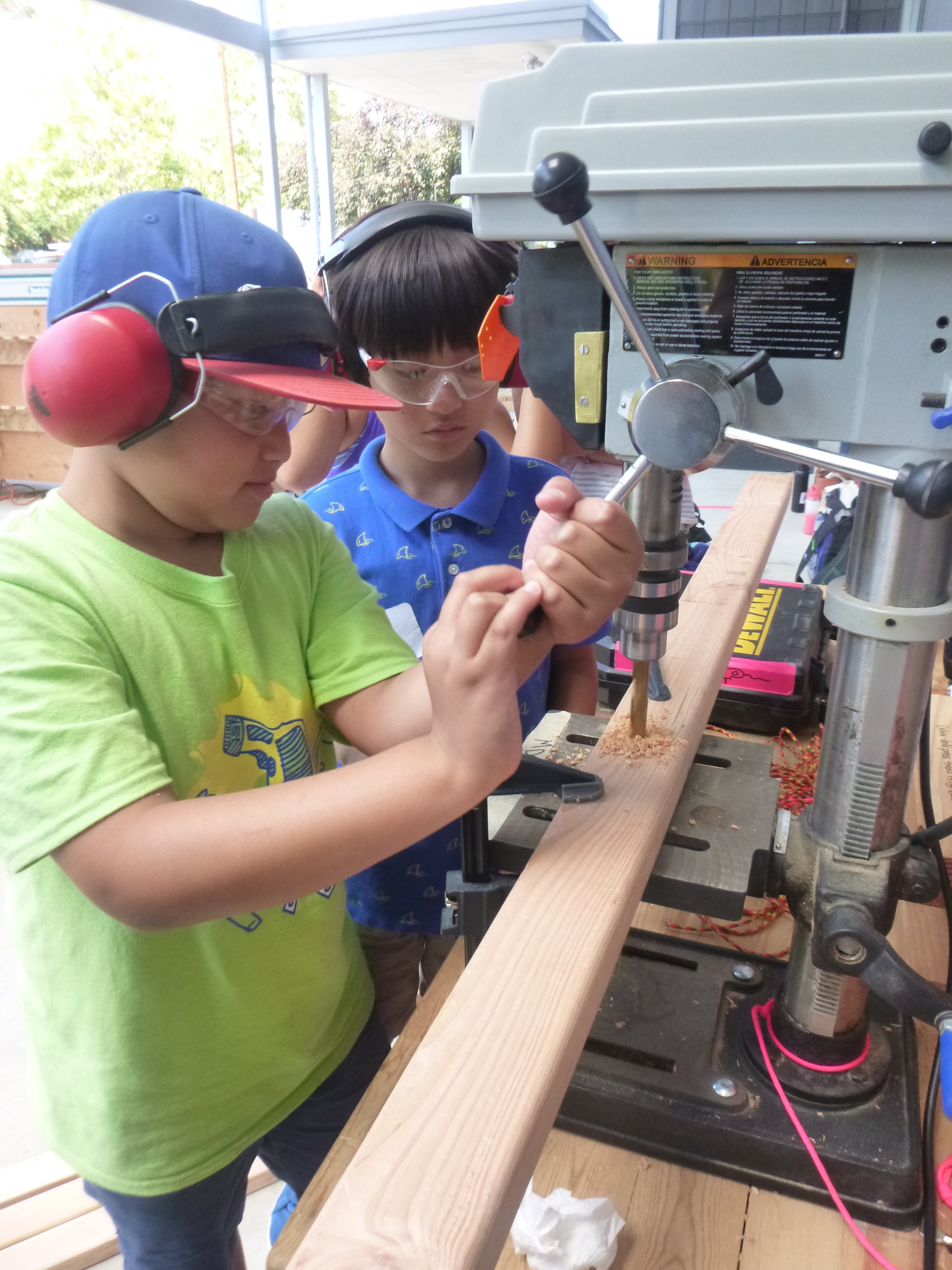 Taelon and Jacob learn how to use a new tool - the drill press.