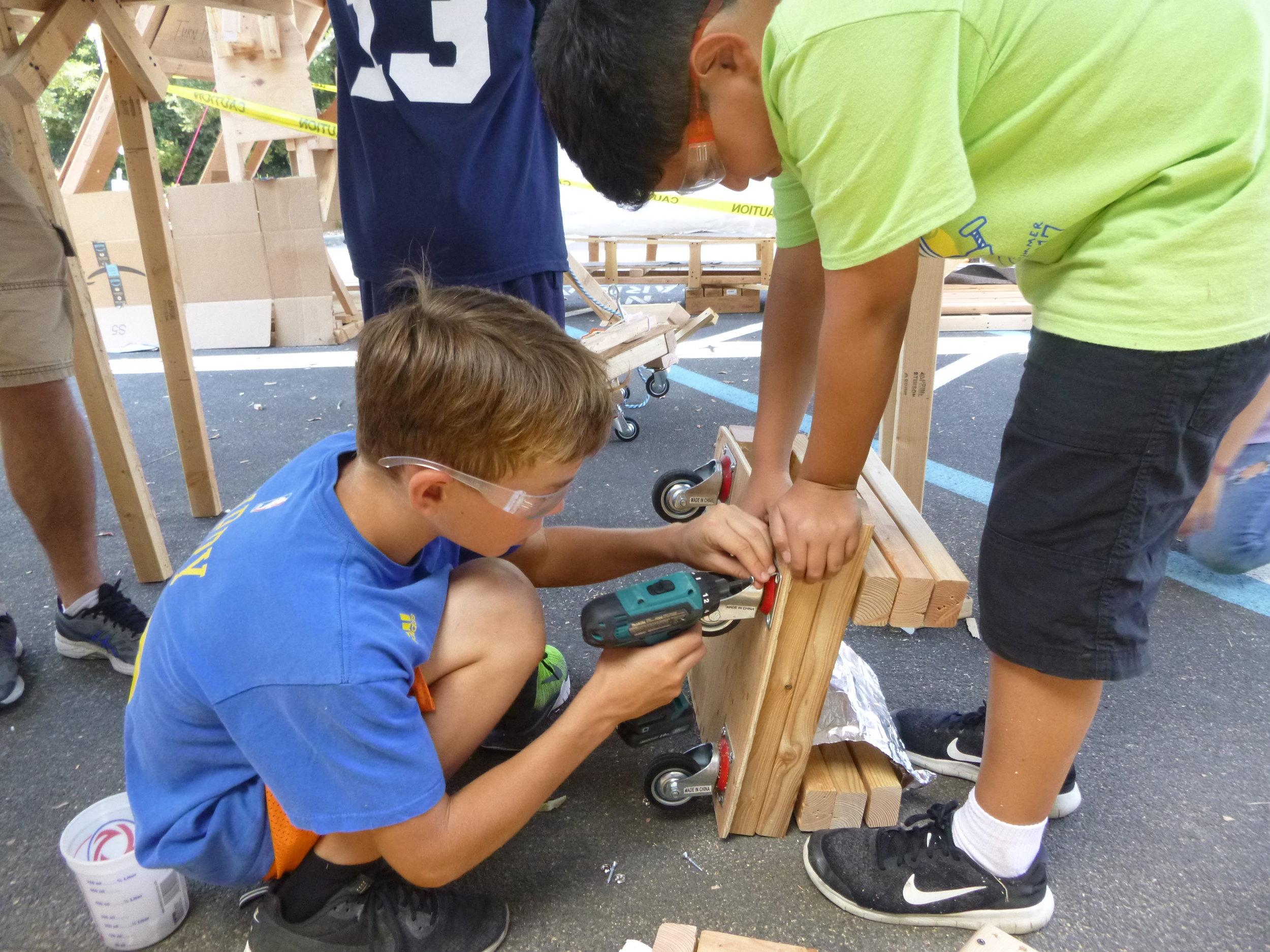 Jaden and Taelon adjusting the monorail wheels.