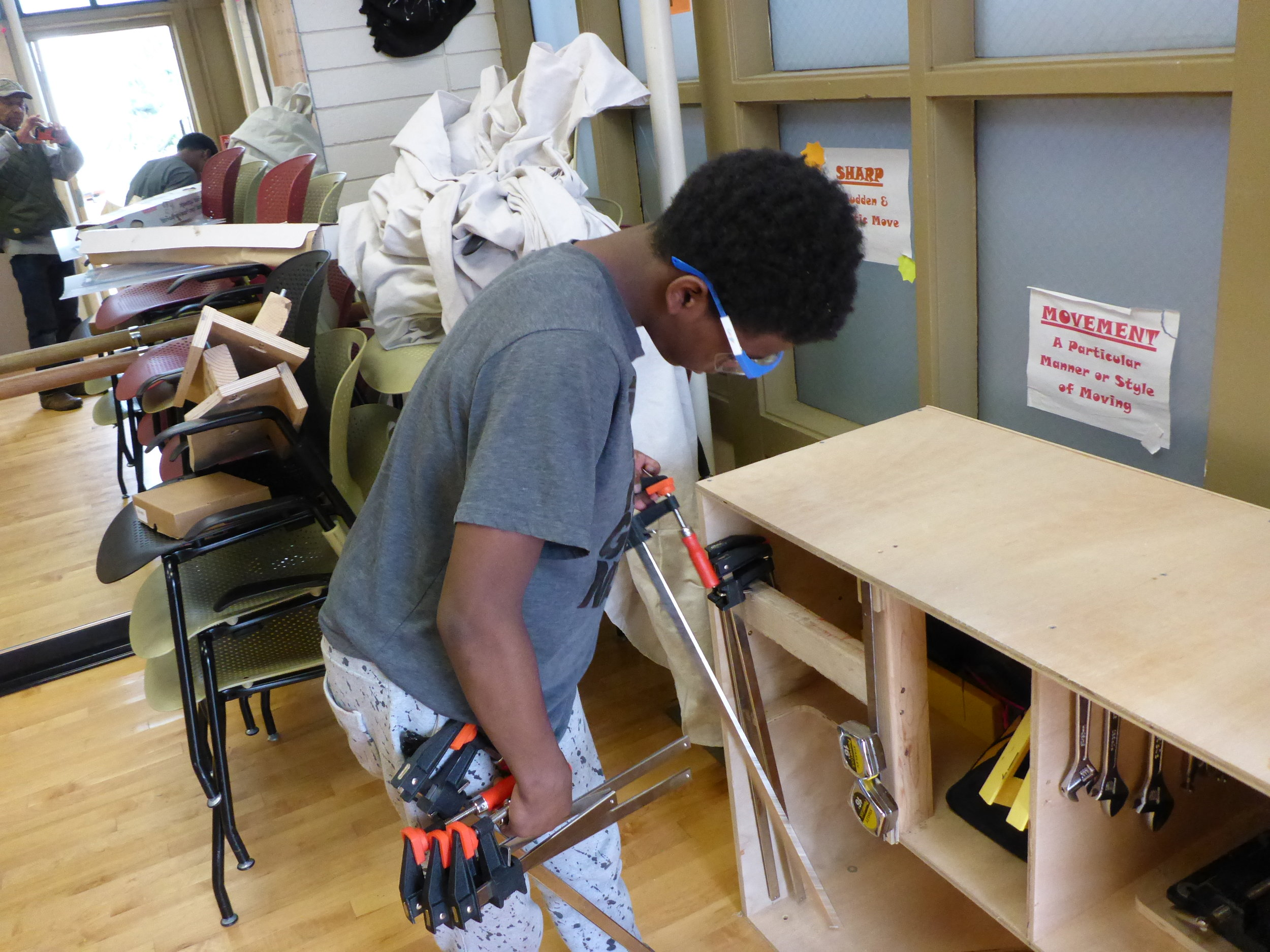Malieke grabs a couple handfuls of clamps. We needed them to hold our clubhouse together before we could secure it with screws.