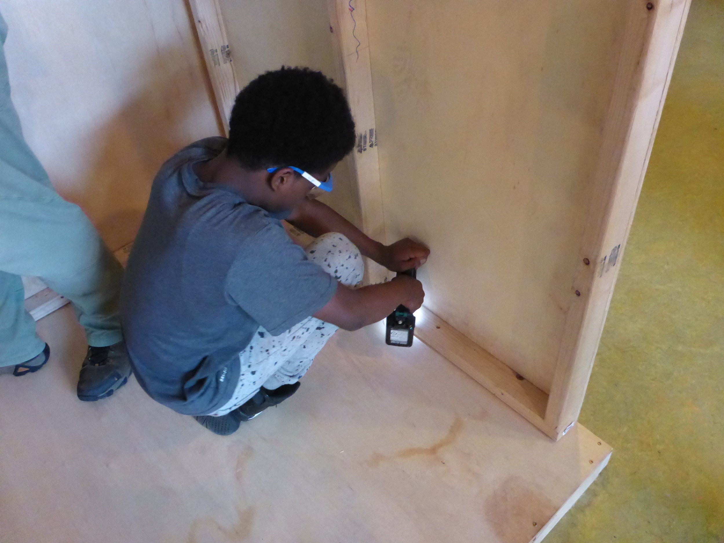 Malieke secures the floor with lots of screws. Better safe than sorry when attaching your house to it's foundation!