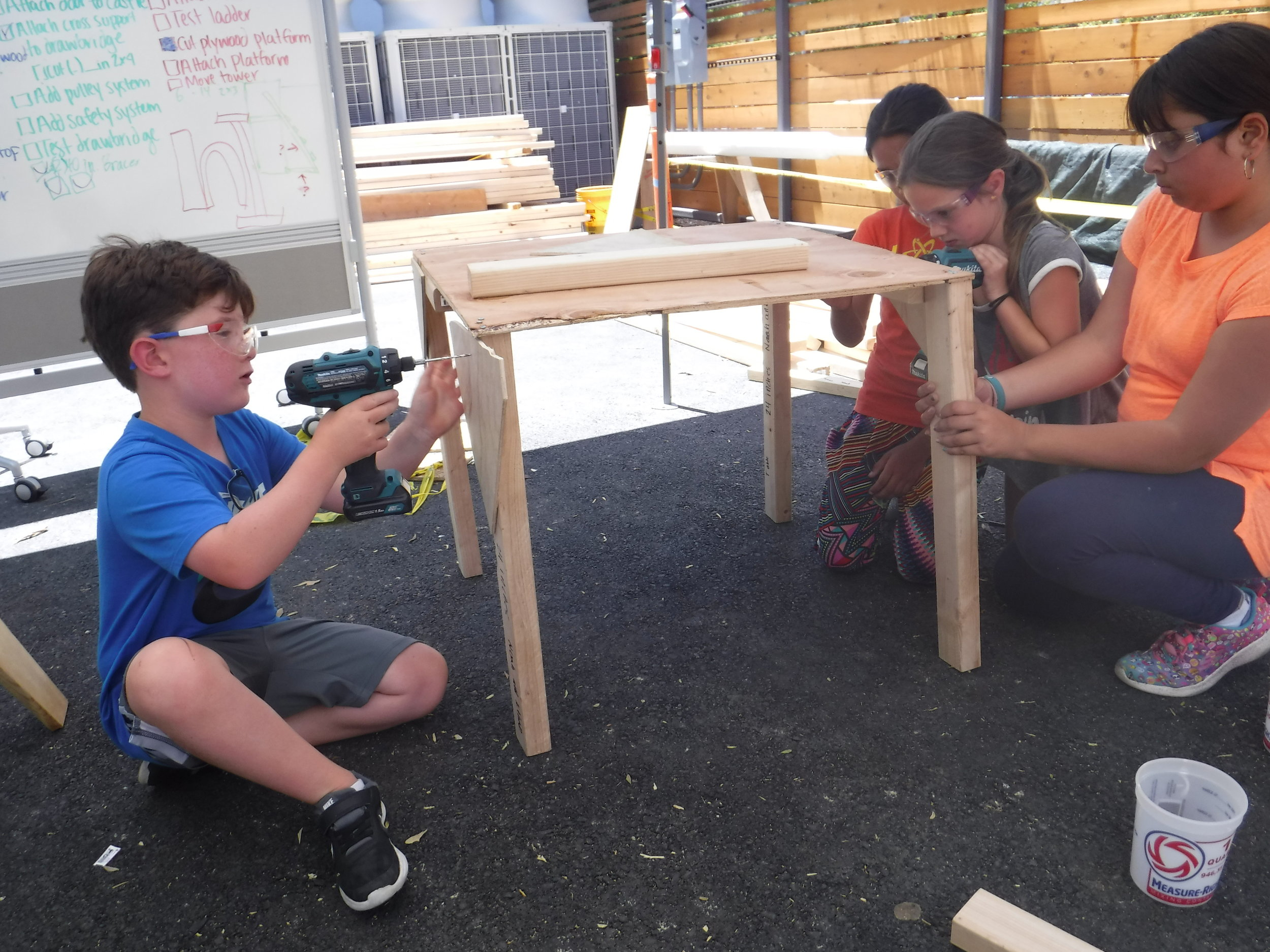 """Our bench was so sturdy and comfortable that I wanted to take it home for my garden but our table was a bit too wobbly. So a collaborator introduced the idea of """"gussets,"""" triangular pieces of plywood that help reinforce two pieces of wood. The team got busy attaching gussets to the table legs and the problem was solved."""