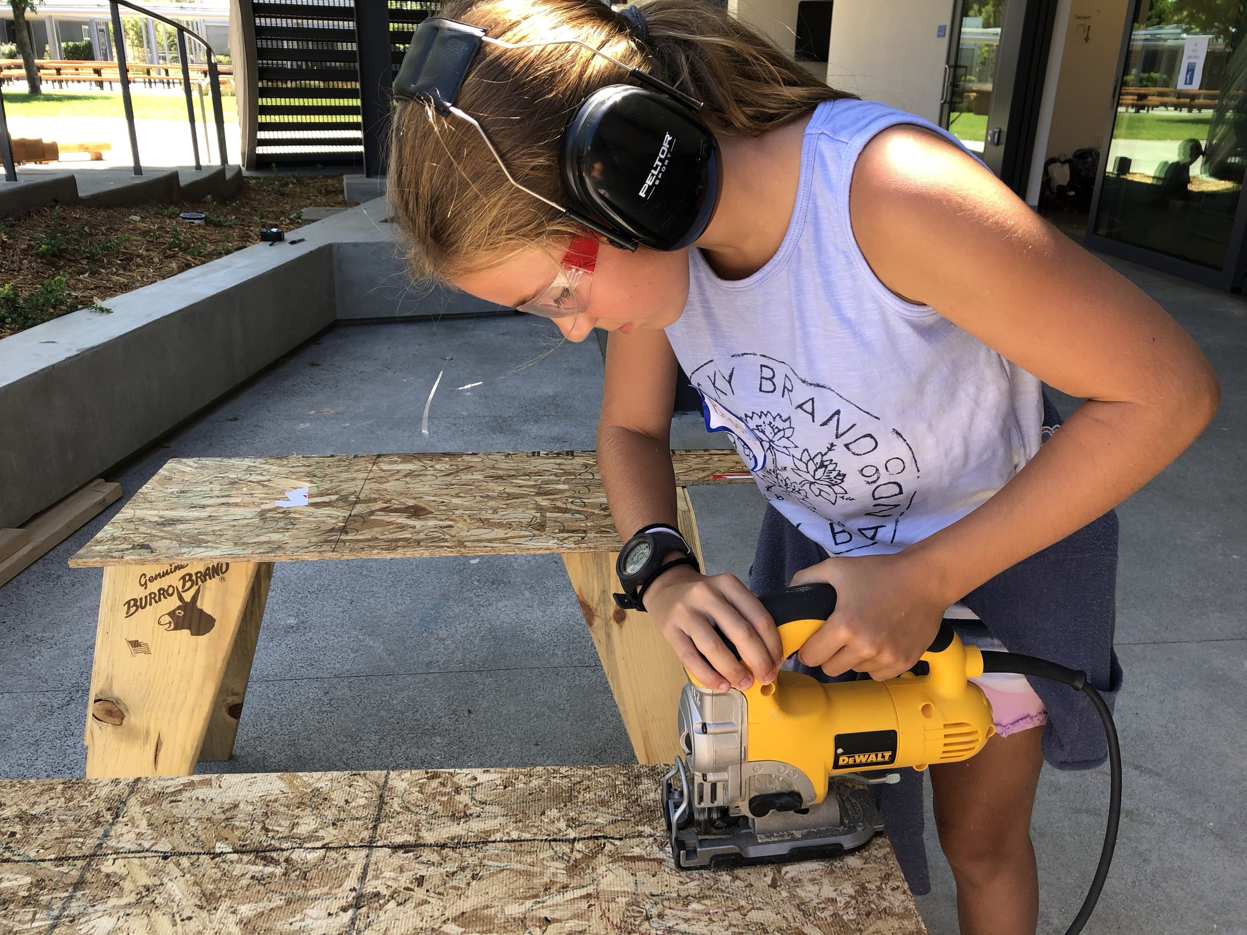 """It takes several steps to be ready to use the jigsaw: measure and draw lines, clamp wood to sawhorse, put on ear protection and goggles, """"is everybody ready?"""" safety call, and then it's time to cut."""