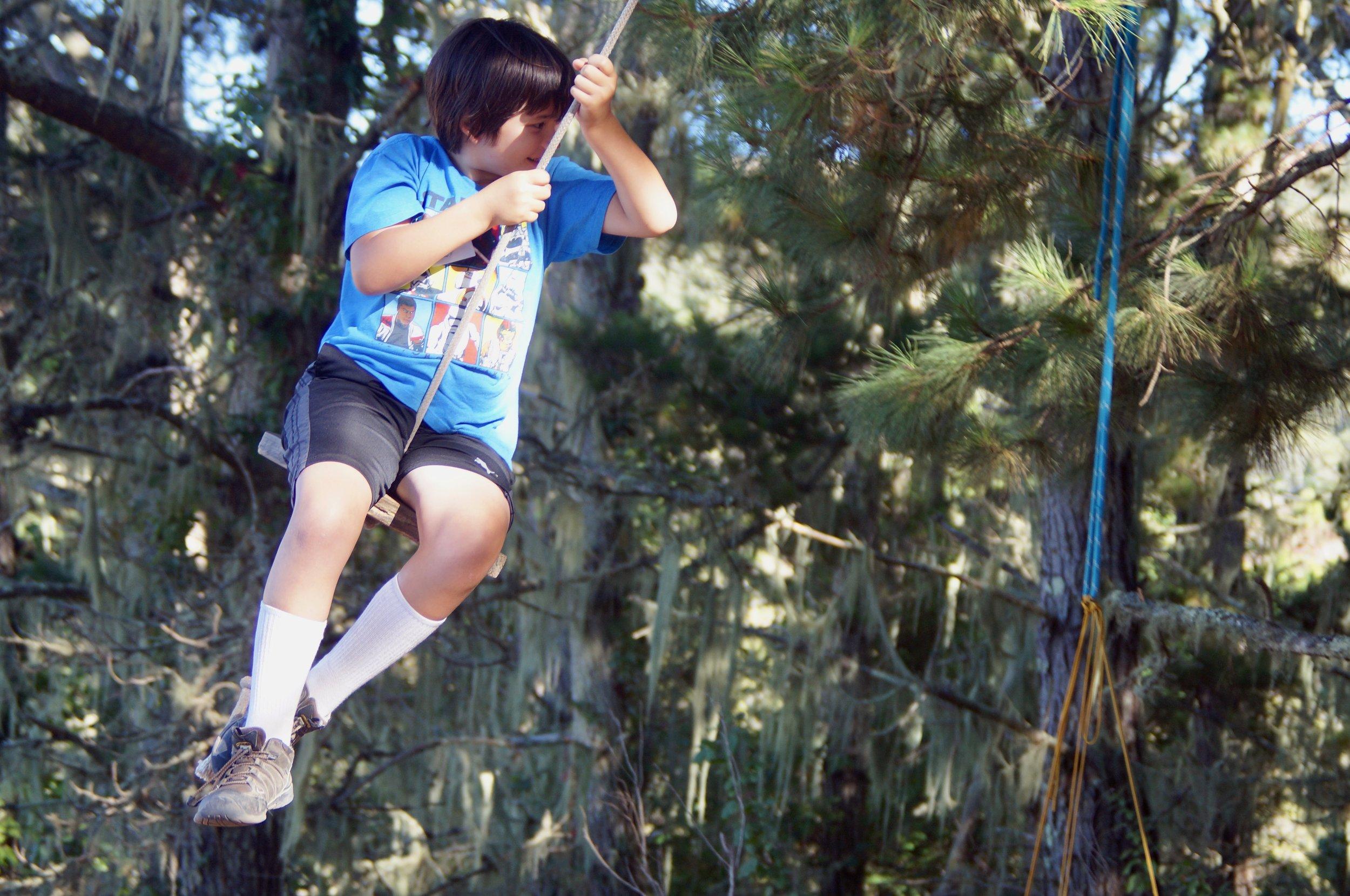 Alex swings joyfully on the tree swing.