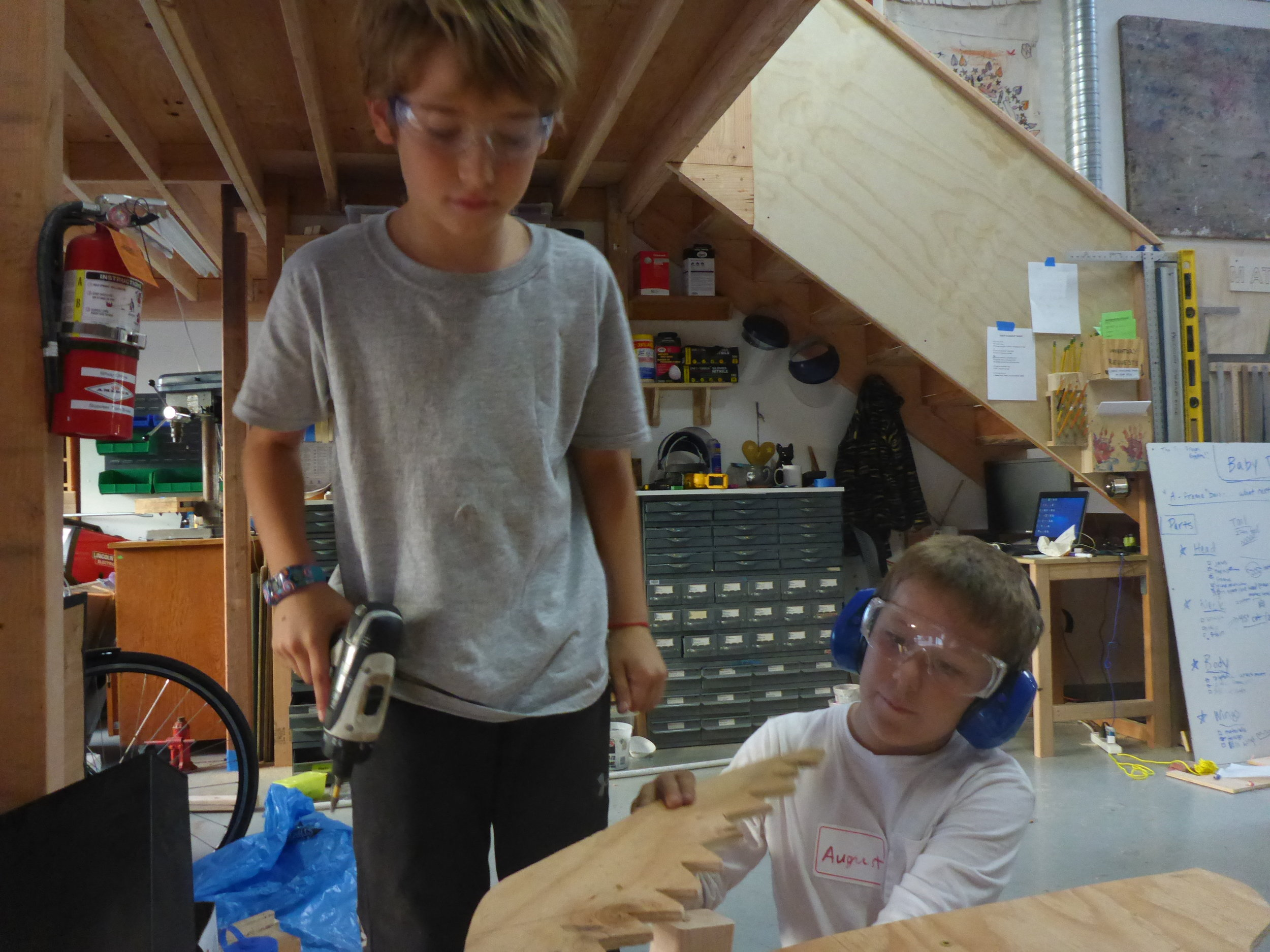 August recruited Jackson to help him build some cross supports for the dragon head he's been carefully crafting.