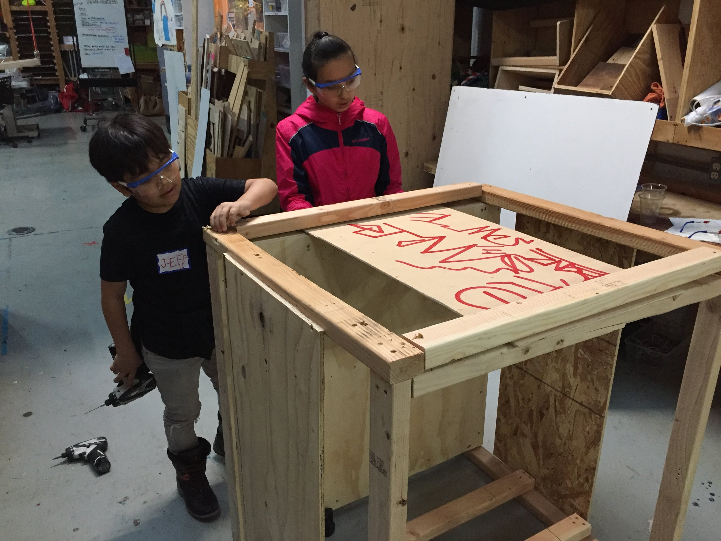 A job well done! Javier and Noehmy test out the movable door/entrance of the elevator.