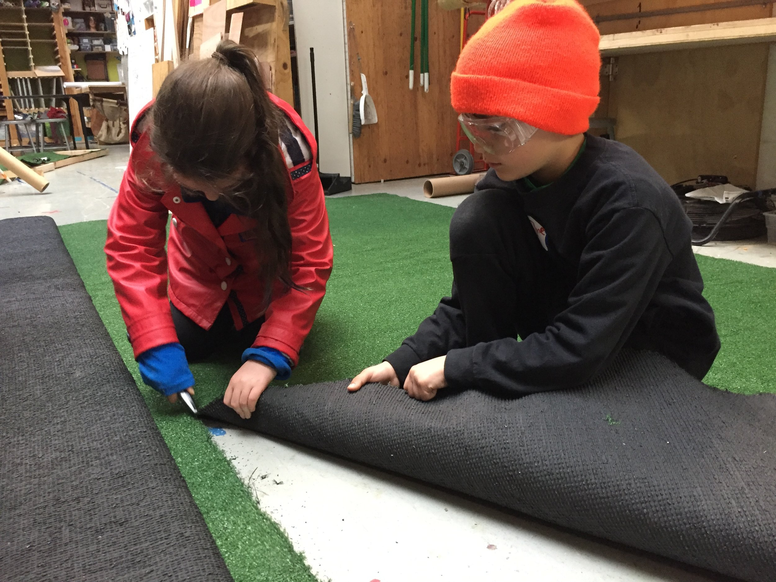 Keira and Zane cut sections of the putting green for the Mini Golf course.