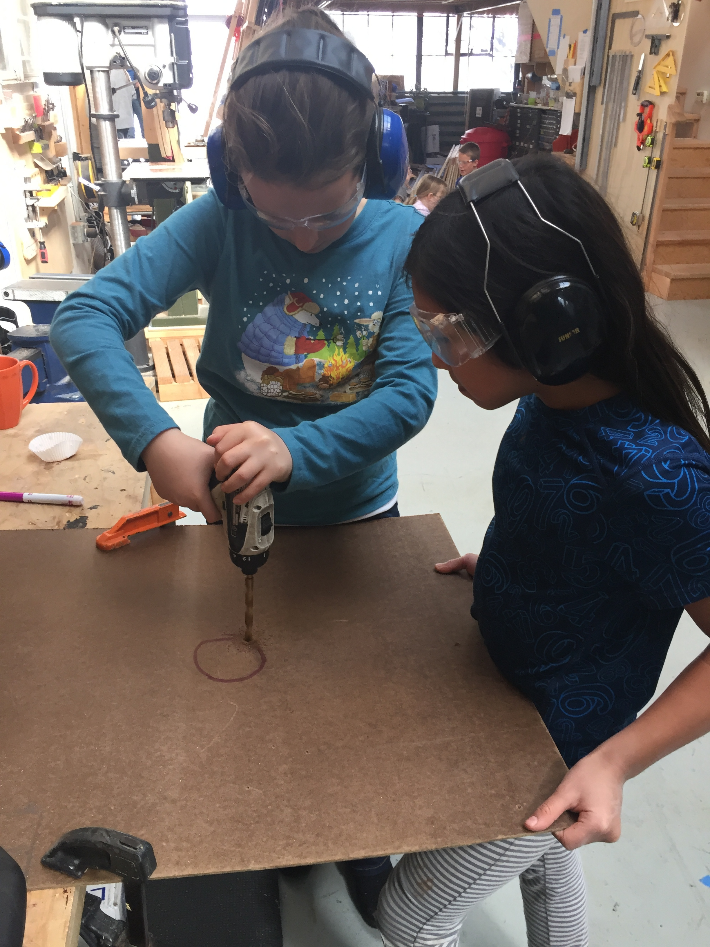 Keira and Ayana use the chuck drill to make a hole for the jig saw blade so they can cut out the most important part of the course!