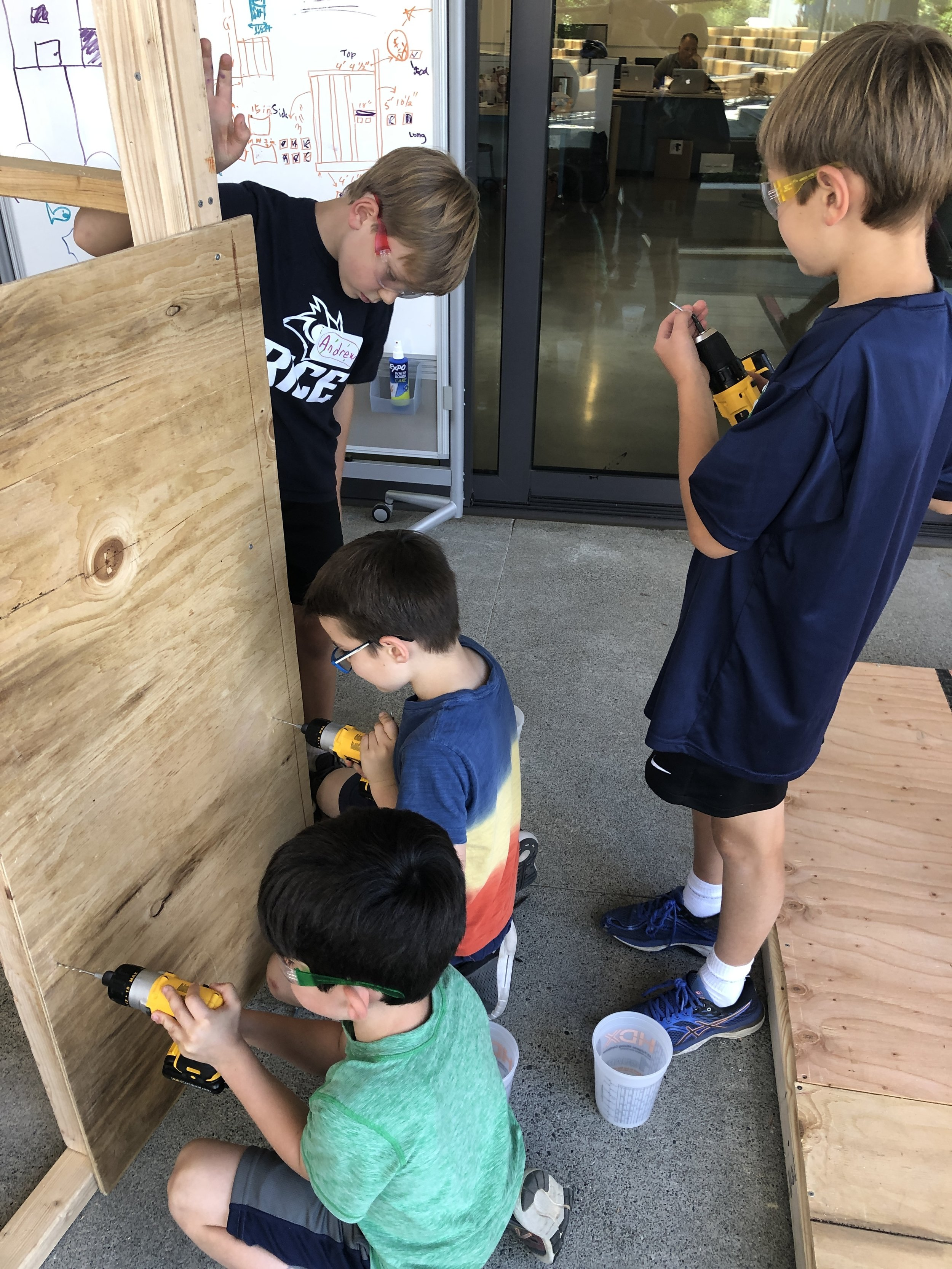 Everybody is helping to attach plywood to the walls