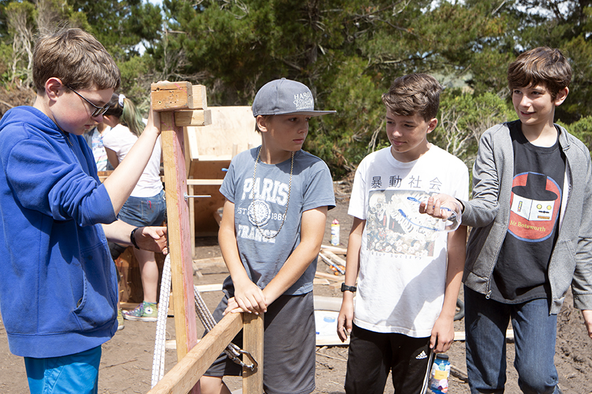 Zachary, Lars, Miller and Charlie discuss possible solutions to safely operating the catapult obstacle.