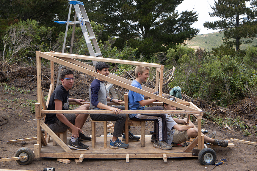 Tinkerers, Cole, Max, Daniel and Tom test the compartment spacing of their rover while sitting on chairs they installed for themselves.