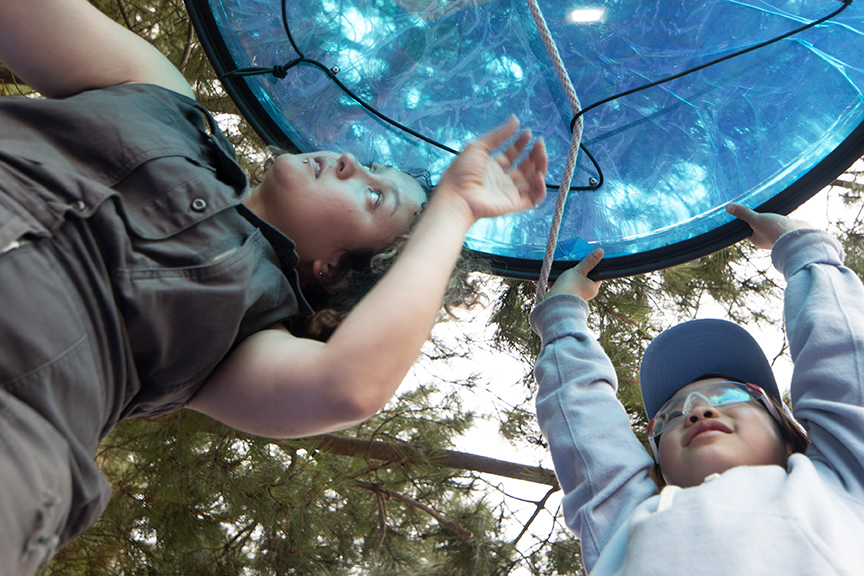 Collaborator, Maddy, and Tinkerer, Emily, hold up a skylight for their shelter while their teammates work to secure it by rope.