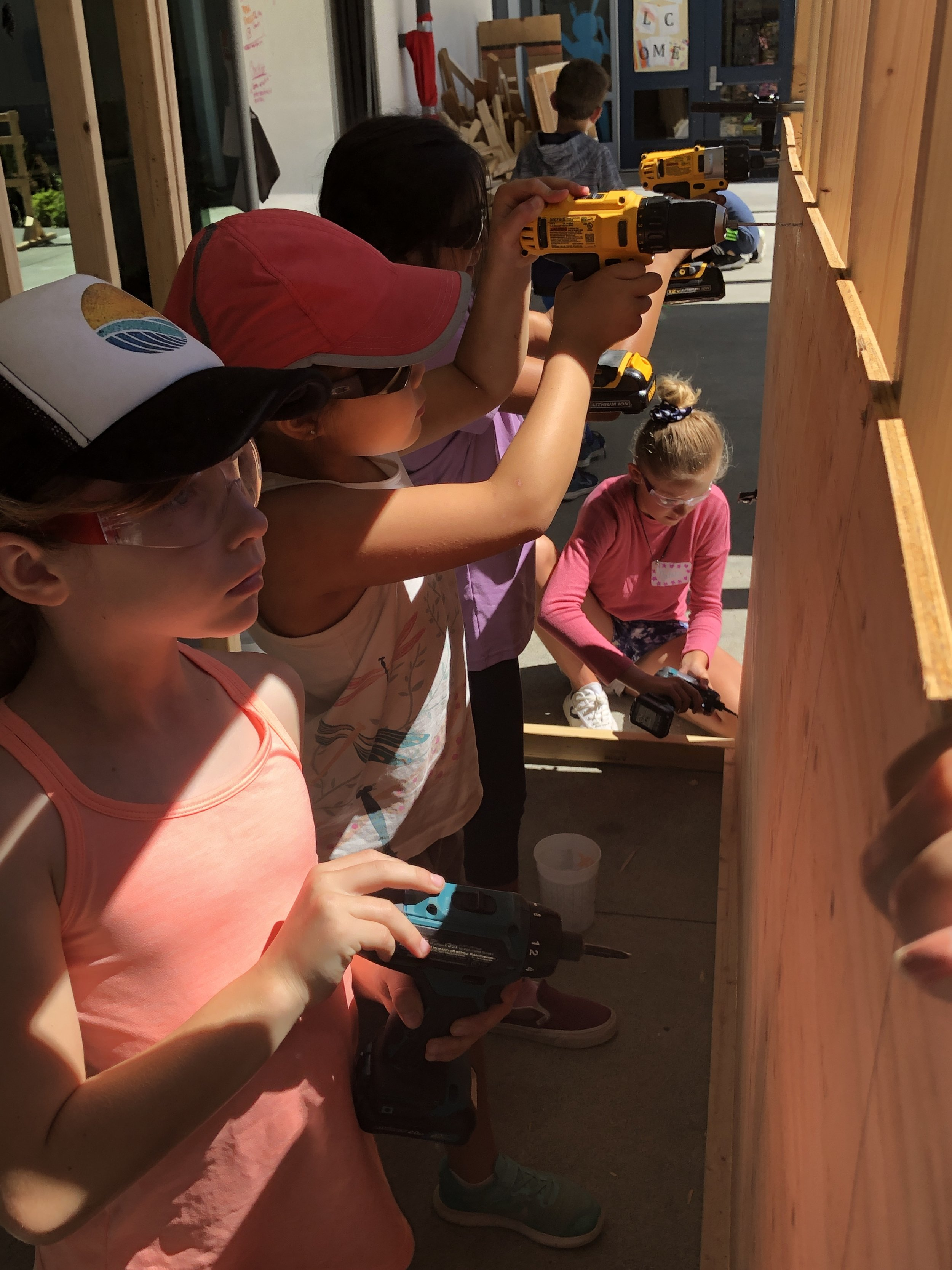 One, two, three, four drills in action to drive screws into the plywood sides of the cave.