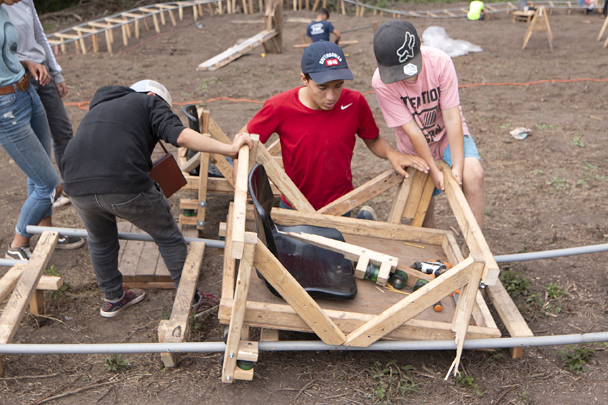 Collaborator, Viggo, and senior Tinkerers, Alex and Reis, work to remove a roller coaster cart with a broken wheel block.