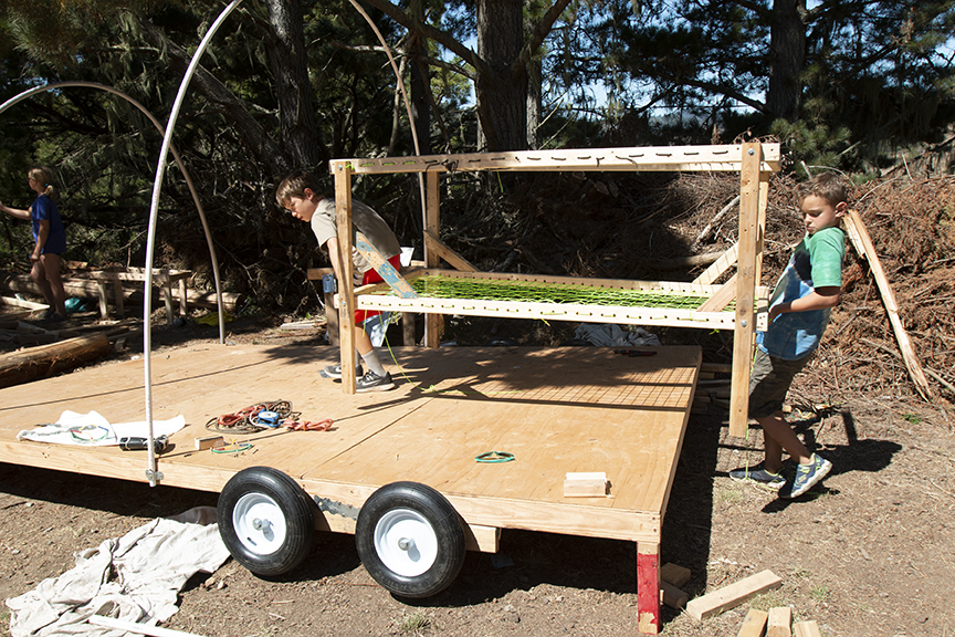 Junior Tinkerers, Isaac and Charlie, move a bunk bed onto their RV platform.