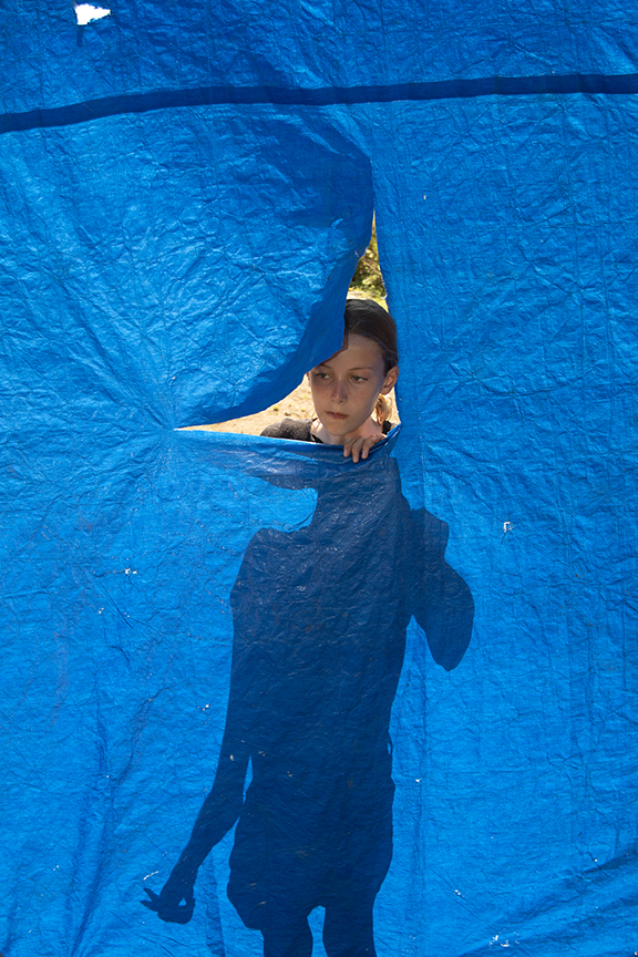 Senior Tinkerer, Kate, peeks through a window she is cutting out of Bessie the Blue Cow's tarp covering.