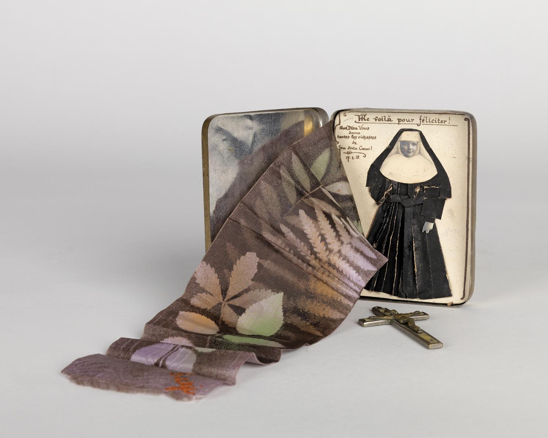 World War I-period curiosity with original photograph of a nun, cross, photogram and handwritten notations. Circa 1918