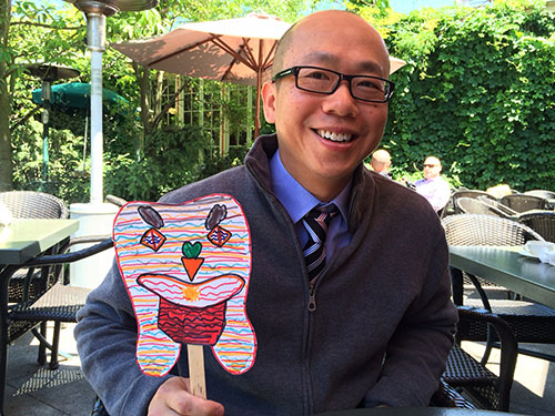 Dr. Allen Tam raises his adorable tooth paddle at the Creston Children's Dental Clinic Fundraiser.