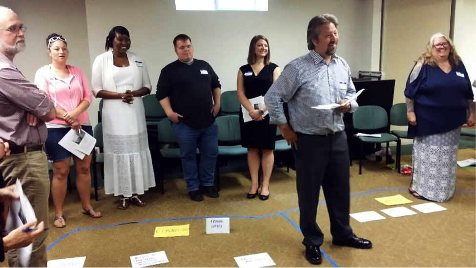 Several participants stand in a circle around blue tape and pieces of paper laid out on the floor.
