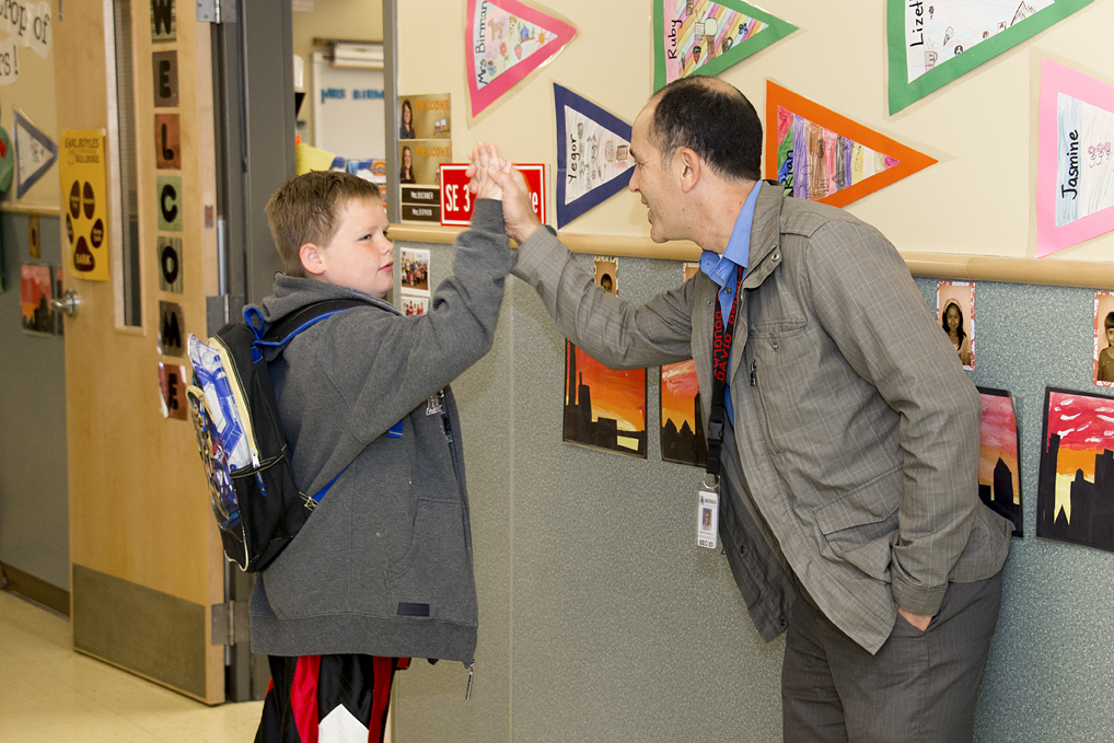 Adult and child high-fiving in a school hallway.