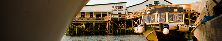 Boats and boardwalk, with Rogue Public House in the background.