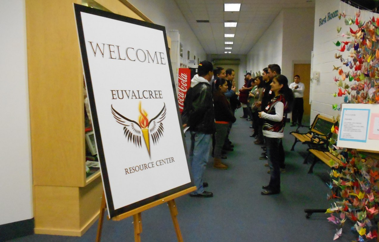 "Two rows of people facing each other. A sign in the foreground reads ""WeLcome Euvalcree Resource Center."""