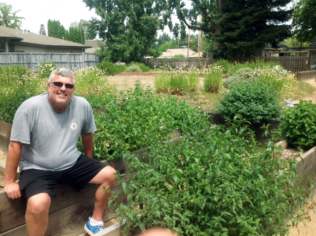 David Fricke, Executive director of Umpqua Valley disAbilities Network, sitting on the edge of one of the raised beds.