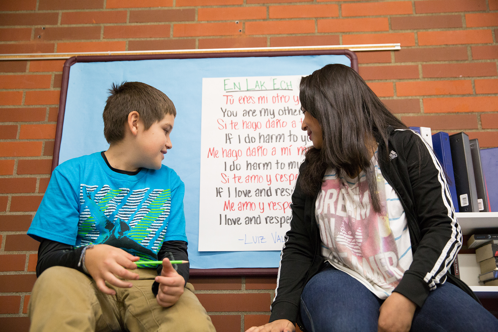 Two youth sitting on a table, looking over their shoulders at a poster with a poem in two languages.