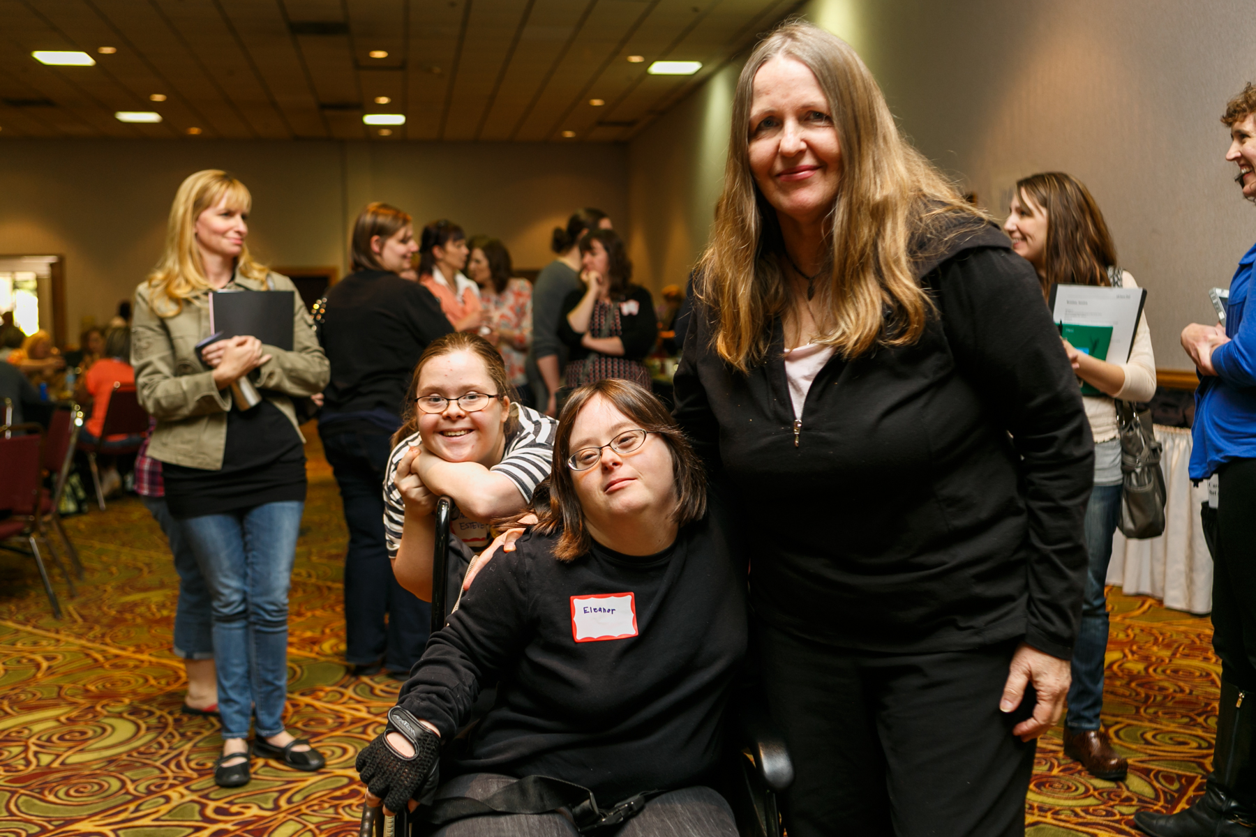Three women pose for the camera in a crowded conference room. Two appear to have Down Syndrome; one is in a wheelchair.