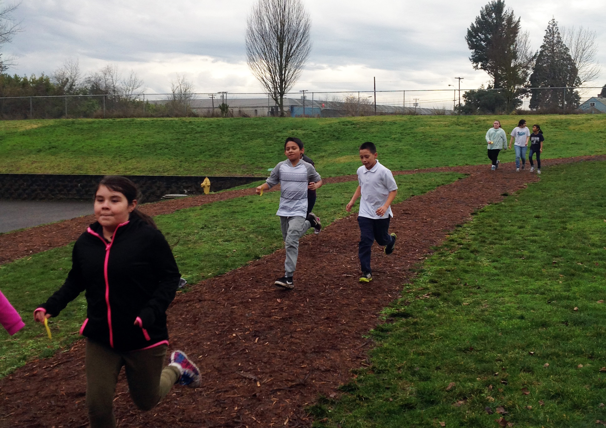 Kids running around a dirt track.