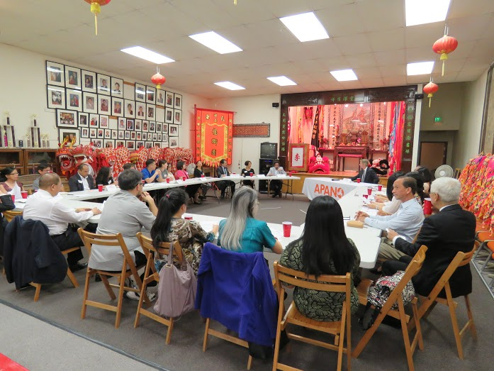 "Several adults sit around a circle of tables. A tablecloth reads ""APANO."" Red lanterns hang from the ceiling. There are banners, flags, signs, etc. with Chinese characters along the back wall."