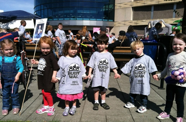"A row of children in oversized t-shirts printed with the words ""Buddy Walk"" hold hands."