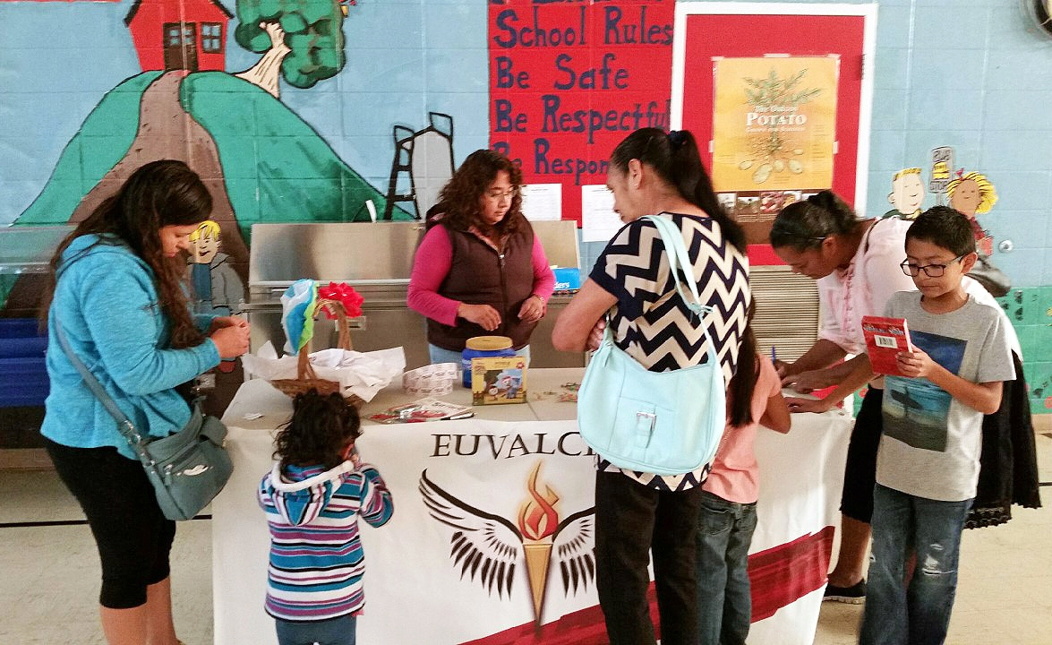 A EUVALCREE Community Organizer provides information on leadership and advocacy courses, and how to become a volunteer, at a table draped with a EUVALCREE banner. Three women and two kids crowd around the table.