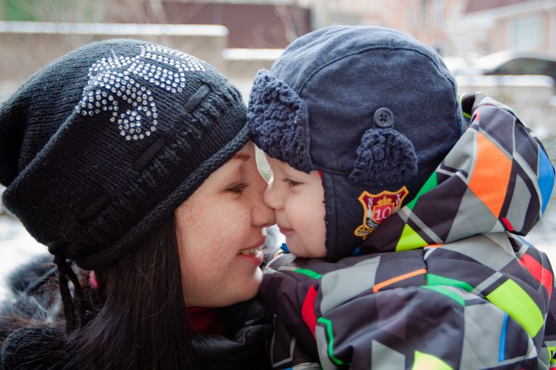 A mom and toddler, bundled up in winter hats and coats, rub their noses together.