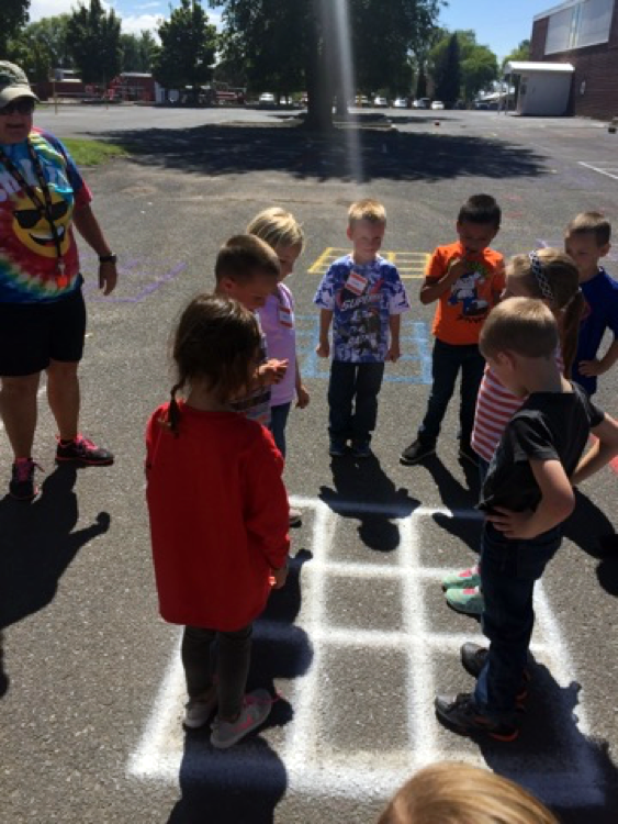 Students stand in and around a grid spray painted on a blacktop.