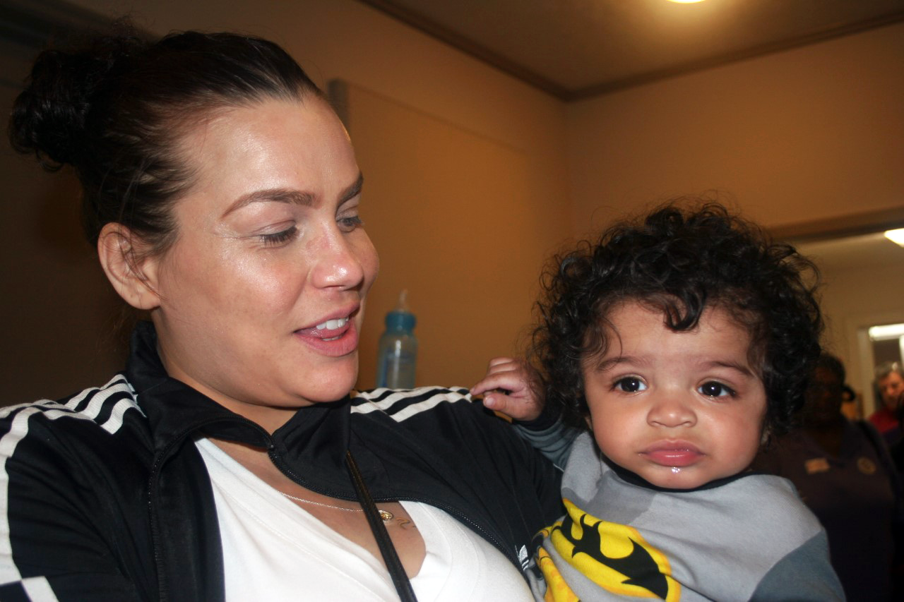 A woman holds a drooling toddler with curly black hair.